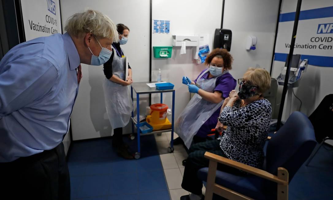 O primeiro-ministro da Grã-Bretanha, Boris Johnson, fala com Lyn Wheeler antes que a enfermeira Rebecca Cathersides administre a vacina contra Covid-19 no Guy's Hospital em Londres Foto: FRANK AUGSTEIN / AFP