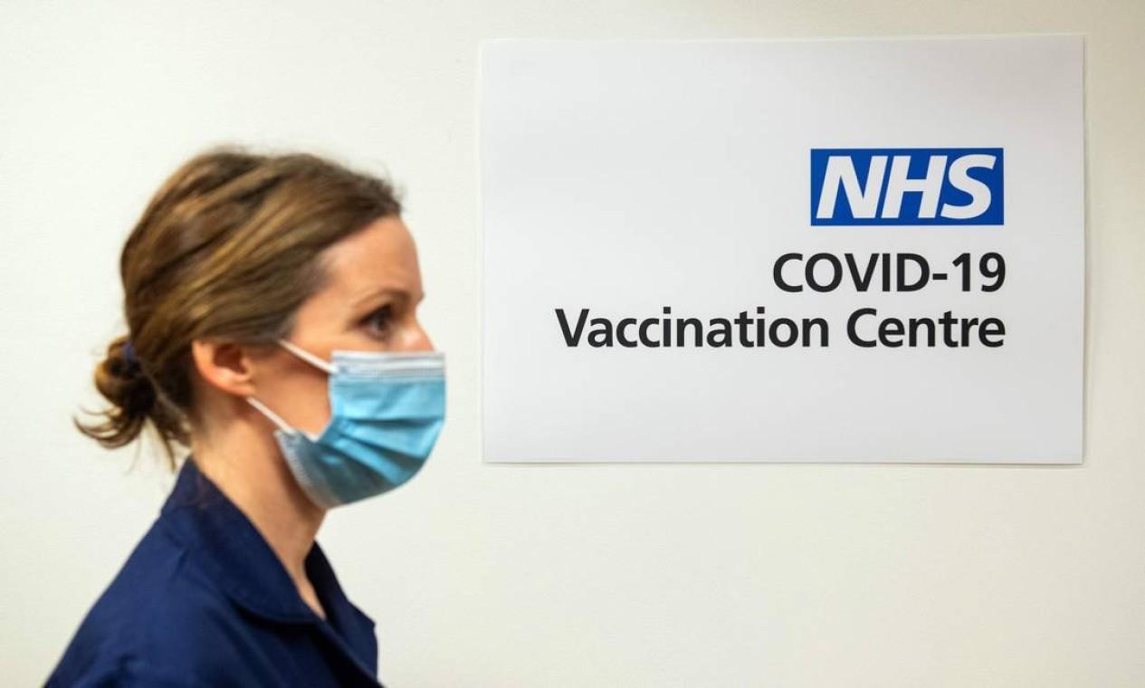 Enfermeira passa por uma placa indicando um Centro de Vacinação Covid-19 no Royal Free Hospital, em Londres Foto: DOMINIC LIPINSKI / AFP
