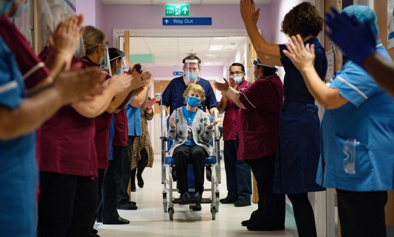 Margaret Keenan, 90 anos, é aplaudida pela equipe ao retornar para sua enfermaria depois de se tornar a primeira pessoa a receber a vacina contra Covid-19, no Hospital Universitário em Coventry, região central da Inglaterra Foto: JACOB KING / AFP