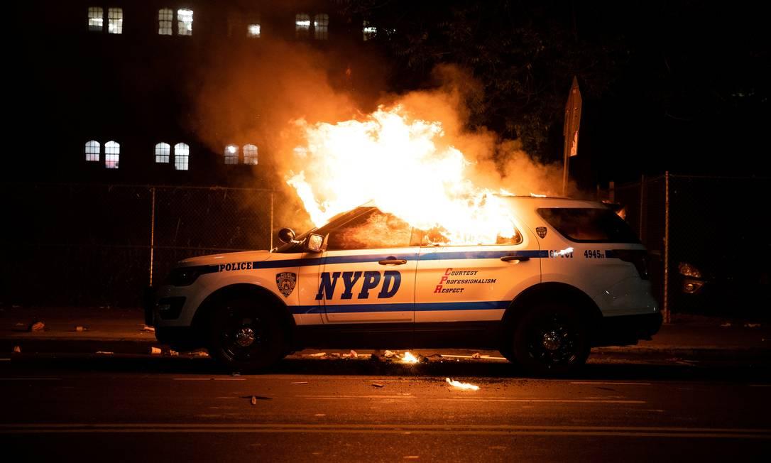 Um carro da polícia de Nova York é incendiado no bairro de Brooklyn enquanto manifestantes entram em confronto com a polícia durante uma marcha contra a morte de George Floyd Foto: JEENAH MOON / REUTERS - 30/05/2020