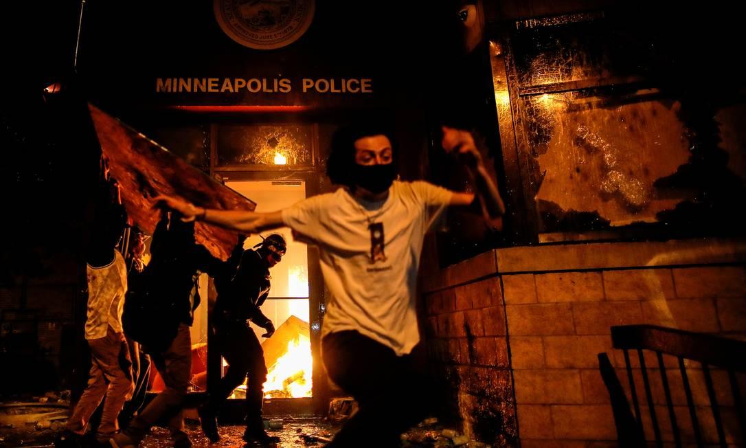 Os manifestantes correm ao atearem fogo na entrada de uma delegacia de polícia depois da divulgação do vídeo em que um policial branco aparece pressionando seu joelho sobre o pescoço de George Floyd, que morreu sufocado pela ação, em Minneapolis, Minnesota Foto: CARLOS BARRIA / REUTERS - 28/05/2020