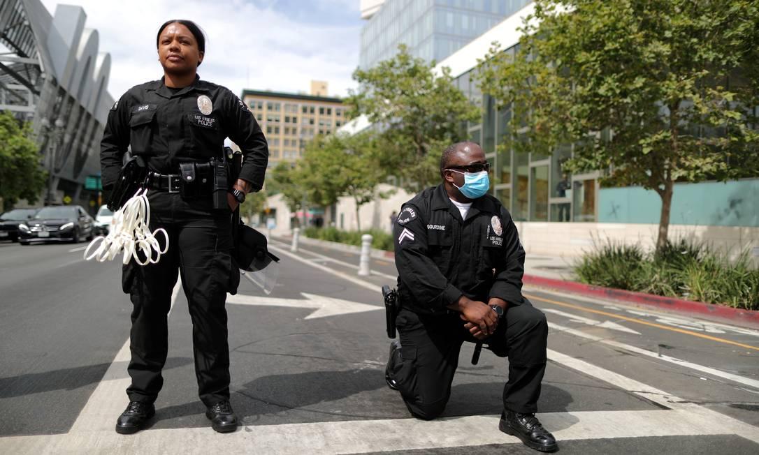 Um policial se ajoelha durante um protesto contra a morte de George Floyd, fora da sede do LAPD em Los Angeles, Califórnia, em 2 de junho Foto: LUCY NICHOLSON / REUTERS - 02/06/2020