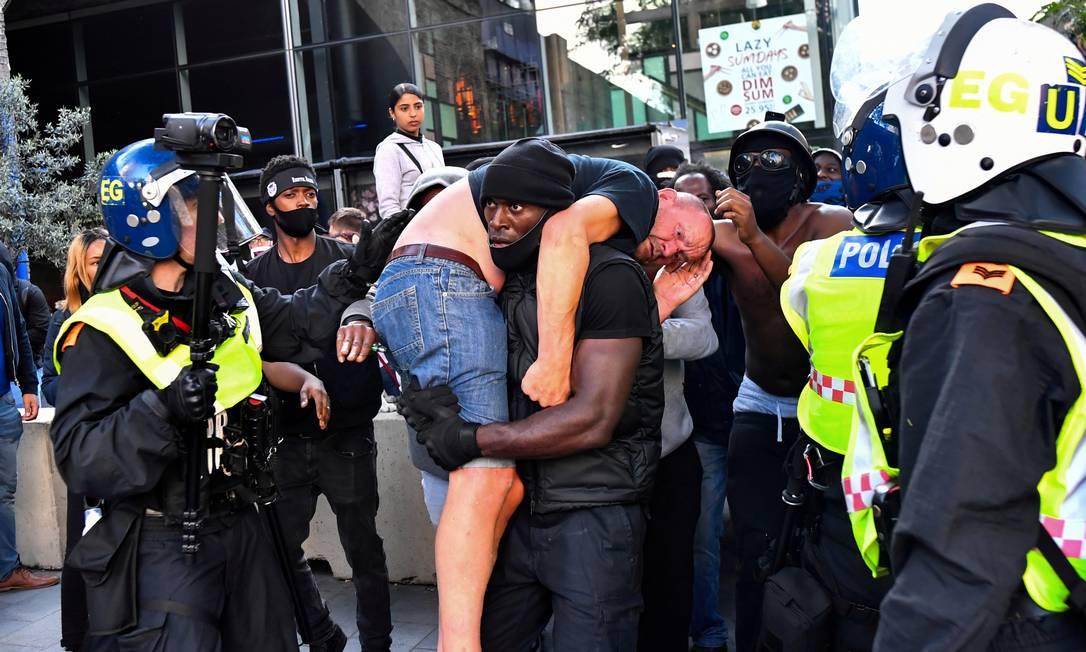 Patrick Hutchinson, um manifestante negro, socorre um contra-manifestante branco ferido, perto da estação de Waterloo, durante um protesto Black Lives Matter, em Londres, em 13 de junho Foto: DYLAN MARTINEZ / REUTERS - 13/06/2020