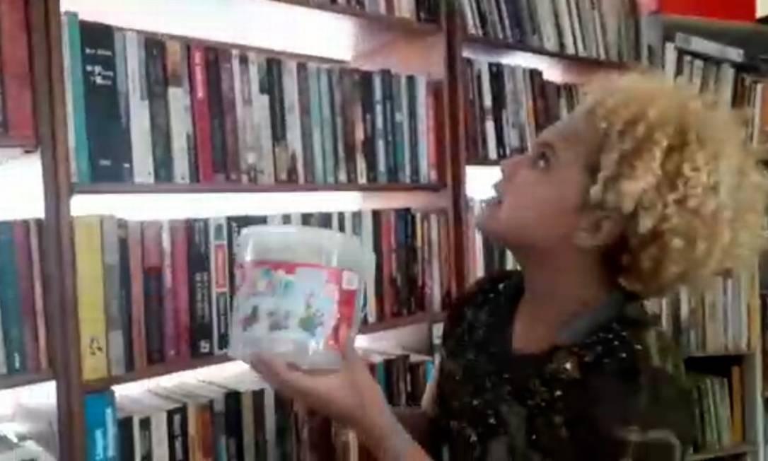 Lua Oliveira mostra pote que tem usado para proteger livros de uma goteira na biblioteca Foto: Reprodução