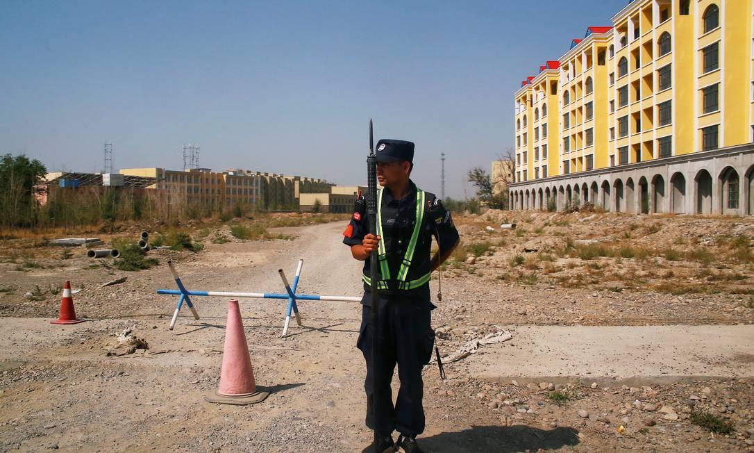 Um policial chinês em uma rua próxima a um dos locais chamados de centro de educação vocacional na província de Xinjiang Foto: Thomas Peter / Reuters