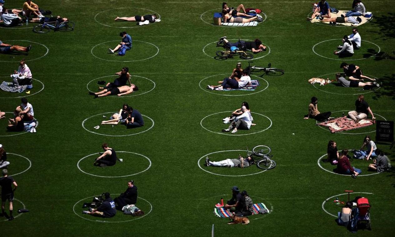 Pessoas mantém distanciamento social marcado por círculo no gramado do Domino Park, em Nova York, EUA Foto: JOHANNES EISELE / AFP