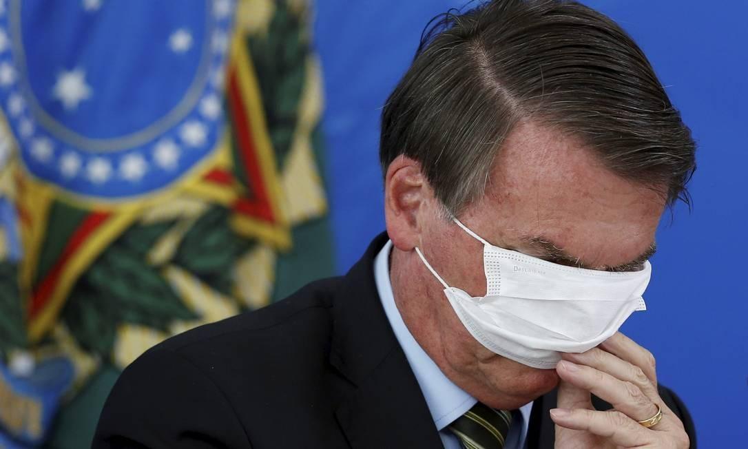 Tapando os olhos. O presidente Bolsonaro se atrapalha com a máscara de proteção durante o anúncio, em março, das primeiras medidas do governo para o combate à pandemia Foto: Pablo Jacob / Agência O Globo - 18/03/2020