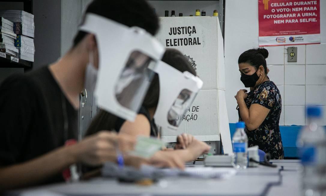 A eleição na pandemia. Mesários usam máscara e escudo facial em posto de votação localizado em escola na Rocinha. Medidas de precaução contra a Covid-19 marcaram o comparecimento dos eleitores às urnas Foto: Hermes de Paula / Agência O Globo - 15/11/2020