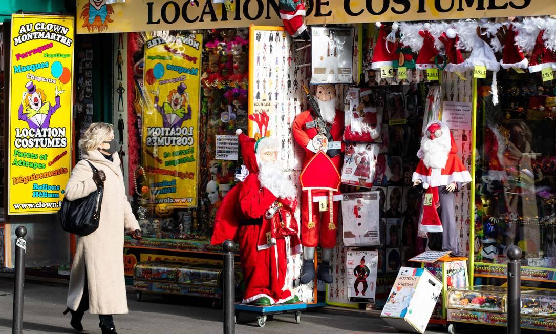 Mulher passa por uma loja de aluguel de fantasias, em Paris: governo anuncia toque de recolher Foto: JOEL SAGET / AFP