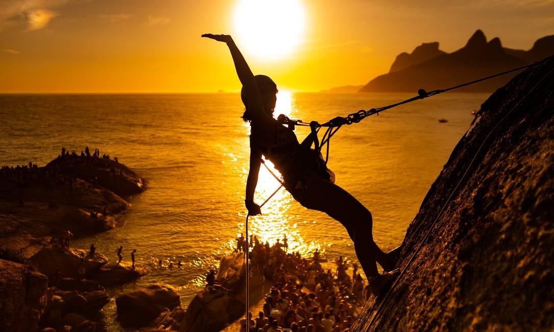 Bem-vindo 2020. Uma mulher pratica rapel no Arpoador enquanto multidão se reúne para assitir ao pôr do sol no primeiro dia do ano, uma tradição carioca Foto: Roberto Moreyra / Agência O Globo - 01/01/2020