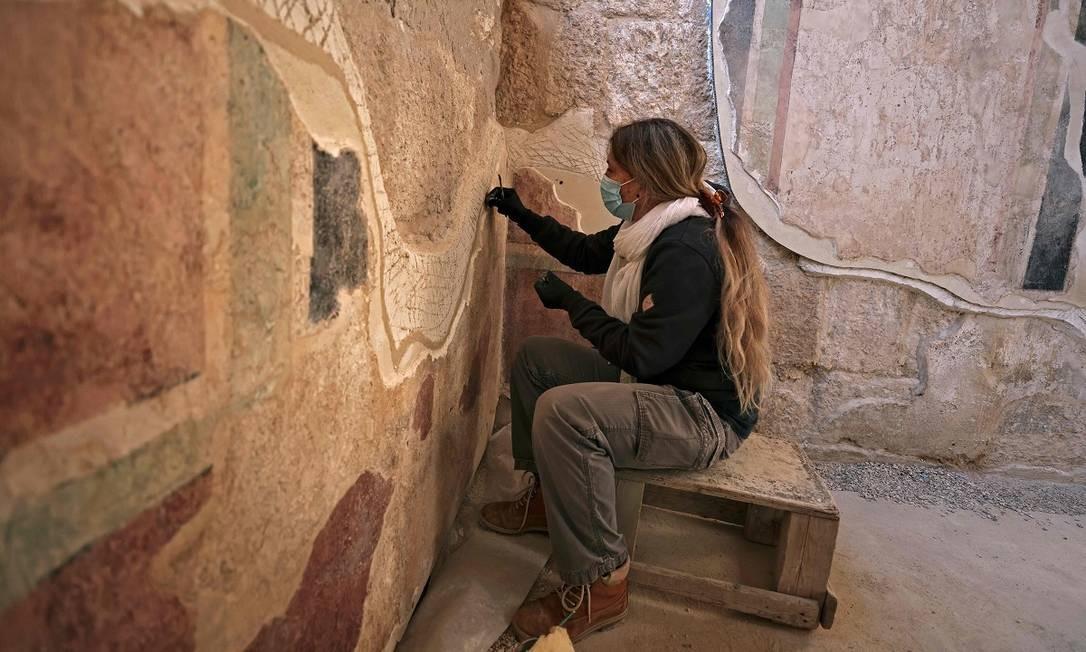 Uma profissional da equipe de restauradores do governo de Israel trabalha nos antigos afrescos da nova ala do palácio de Herodes Foto: MENAHEM KAHANA / AFP