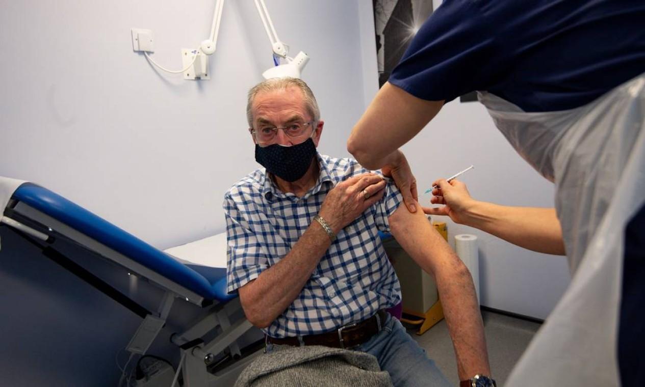 Gerry Hughes, 81 anos, recebe uma dose da vacina Pfizer/BioNTech na Feldon Lane Surgery, em Halesowen, a oeste de Birmingham, no centro Inglaterra Foto: JACOB KING / AFP