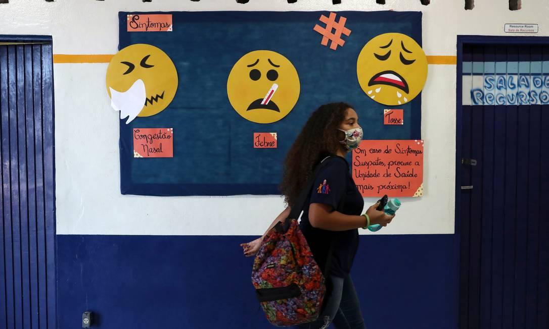 Aluna diante de cartazes sobre o coronavírus na Escola Professor Milton da Silva Rodrigues em São Paulo, em novembro de 2020 Foto: Amanda Perobelli / Reuters
