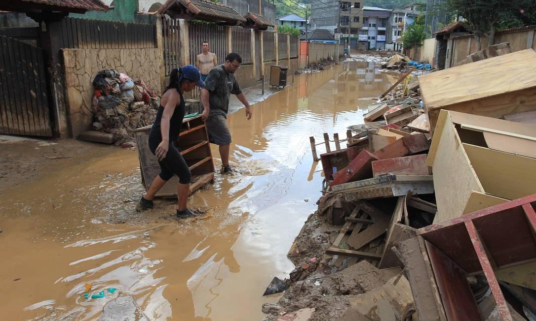 Casal retira de casa móveis danificados pela chuva no bairrro Conselheiro Galvão. Foto: Marcelo Theobald / Agência O Globo - 18/01/2011