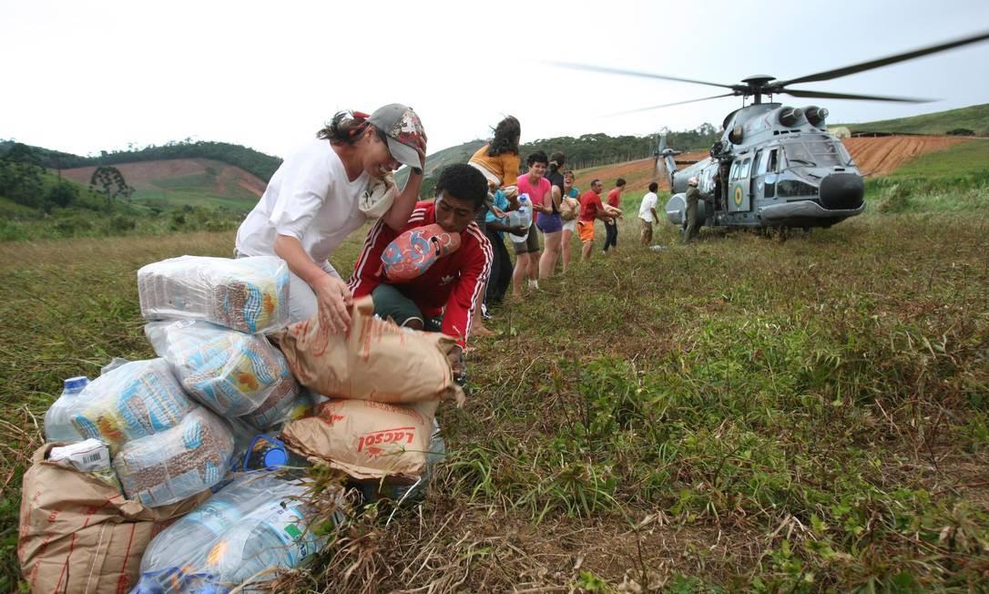 Moradores isolados recebem doações com ajuda de helicóptero da Marinha no bairro Campo do Coelho, em Nova Friburgo Foto: Marcelo Piu / Agência O Globo - 18/01/2011