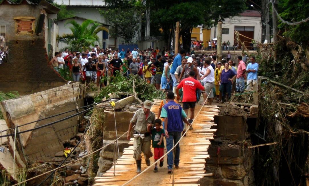 Pessoas aguardam para atravessar ponte de madeira ligando bairro de Bom Jardim ao centro da cidade Foto: Thiago Freitas / Agência O Globo - 14/01/2011