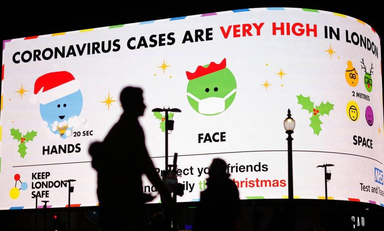 Em Londres, pedestres passam diante de um painel com informações sobre cuidados para evitar a COVID-19 e o aumento do número de casos da doença. O primeiro-ministro britânico, Boris Johnson, anunciou neste sábado (19) que Londres e o sudeste da Inglaterra passam do nível 3 de restrições contra a Covid-19 para o nível 4, o mais alto Foto: TOLGA AKMEN / AFP