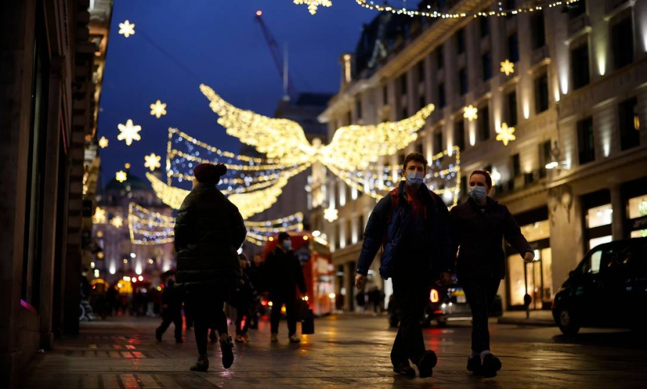 Pedestres e compradores caminham sob as luzes de Natal em uma rua de Londres no último sábado antes do Natal. O Reino Unido desistiu dos planos de aliviar as restrições de circulação de pessoas durante as festas de fim de ano diante de evidências que apontam variante do novo coronavírus 70% mais transmissível Foto: TOLGA AKMEN / AFP