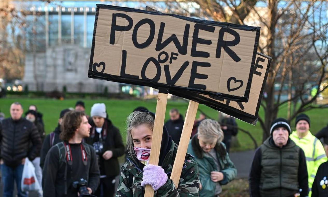 """Manifestante segura um cartaz com a frase """"Poder do Amor"""" durante protesto no centro de Newcastle-upon-Tyne, no nordeste da Inglaterra, contra restrições impostas para conter a propagação do coronavírus Foto: OLI SCARFF / AFP"""