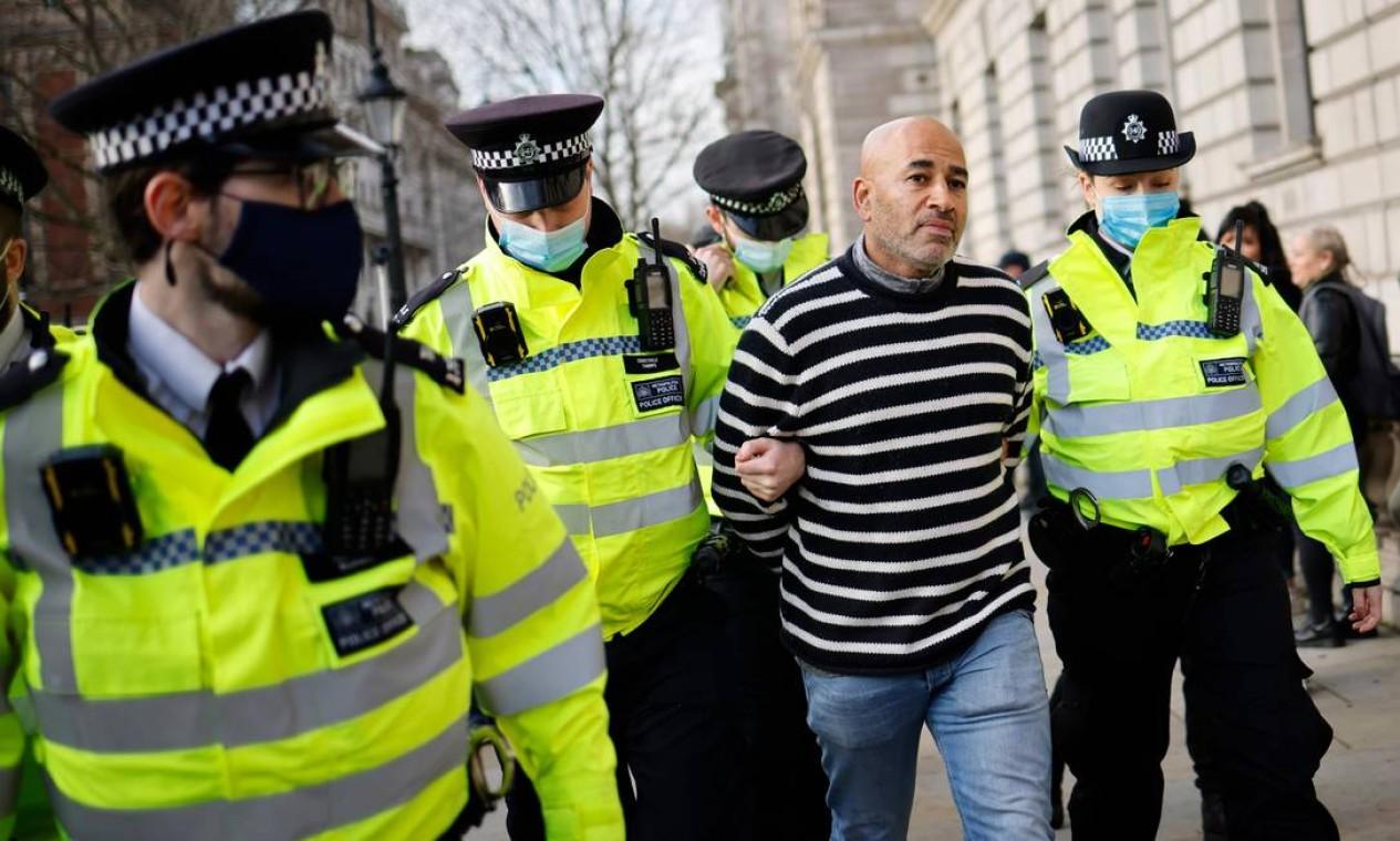 Um manifestante é preso por policiais britânicos durante uma manifestação antilockdown na Parliament Square, no centro de Londres Foto: TOLGA AKMEN / AFP