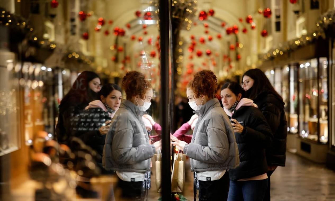 Pessoas observam a vitrine de uma loja com temática de Natal em Londres, enquanto o Reino Unido anuncia edurecimento das medidas restritivas para conter a propagação do novo coronavírus. População deve ficar em casa. Lojas, academias, locais de lazer e de cuidados pessoais serão fechados a partir deste domingo Foto: TOLGA AKMEN / AFP
