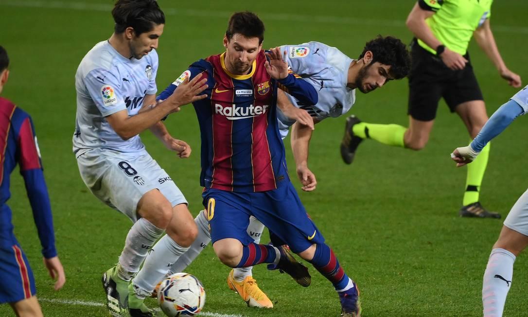 Messi conduz a bola no jogo contra o Valencia Foto: AFP