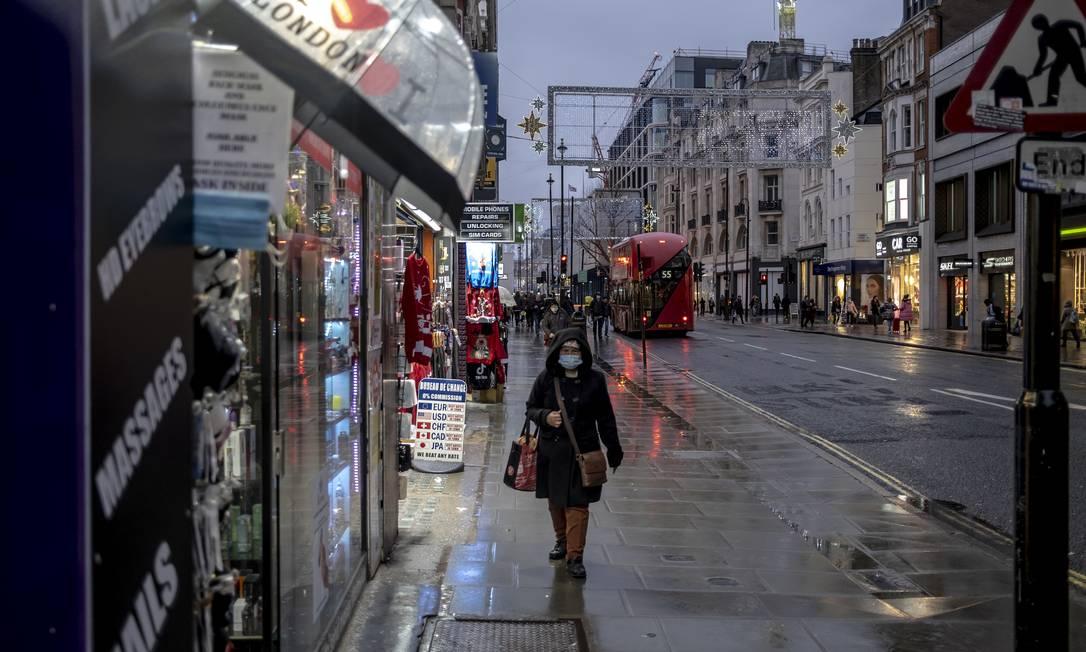 Mulher caminha em rua de Londres no último dia 16, o terceiro após a implementação de medidas restritivas em parte do país Foto: ANDREW TESTA / NYT
