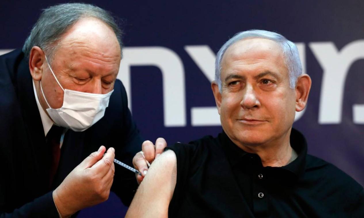 Primeiro-minisrto de Israel, Benjamin Netanyahu, foi o primeiro chefe de estado a receber vacina contra o coronavírus. Ele, que foi imunizado no Sheba Medical Center, maior hospital do país, próximo à capital Tel Aviv. A aplicação do imunizante da Pfizer/BioNTech foi transmitida ao vivo para encorajar a população Foto: AMIR COHEN / AFP