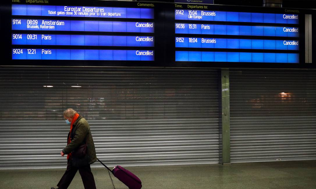 Um viajante anda com a sua mala sob o painel da Eurostar no terminal de trem St Pancras International, em Londres, que informa que todas as viagens internacionais foram canceladas. Foto: HANNAH MCKAY / REUTERS