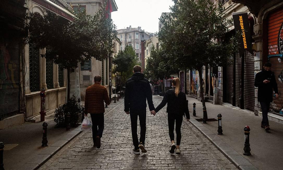 Turistas estrangeiros caminham por uma rua de Istambul, enquanto os moradores estão confinados em suas casas, devido ao aumento de casos de Covid-19 Foto: Bradley Secker / The New York Times