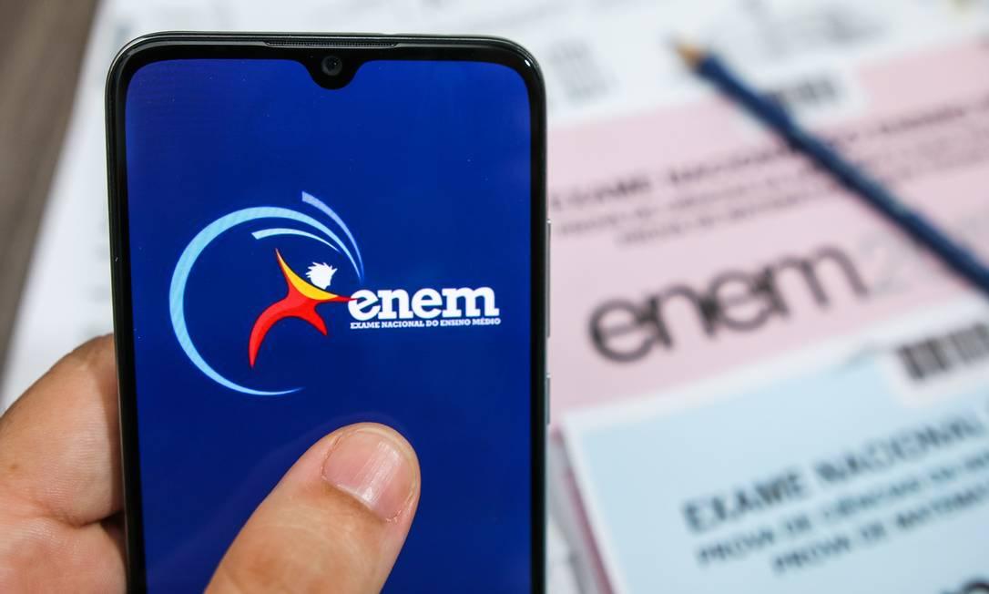 Na foto, mão segura celular com imagem do ENEM 2020 Foto: Cadu Rolim / Agência O Globo