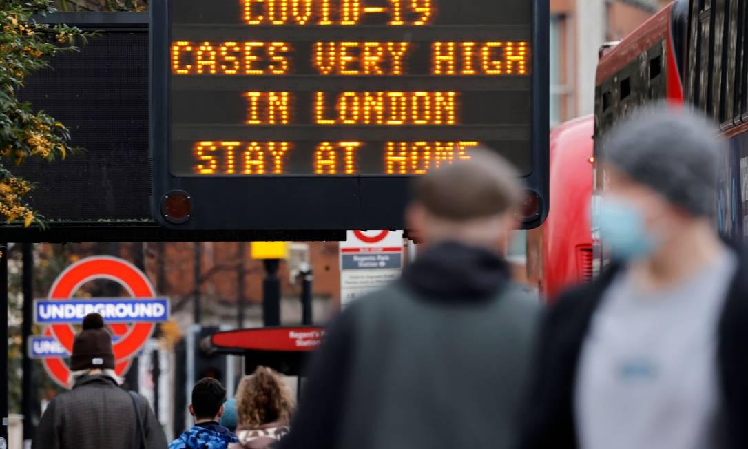 Pedestres, alguns usando máscara, passam por uma placa de alerta sobre o aumento do número de casos de Covid-19 em Londres Foto: TOLGA AKMEN / AFP