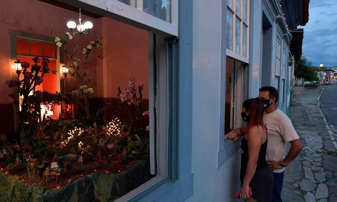 Casal observa da janele o presépio montado na casa de Maria Goretti, um dos mais de 40 que compõem o circuito natalino de Santa Luzia, em Minas Gerais Foto: DOUGLAS MAGNO / AFP