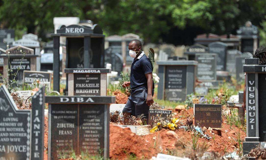 Homem caminha em cemitério de Johannesburgo, na África do Sul, usando máscaras em meio à alta de casos da Covid-19 no país Foto: SIPHIWE SIBEKO / REUTERS