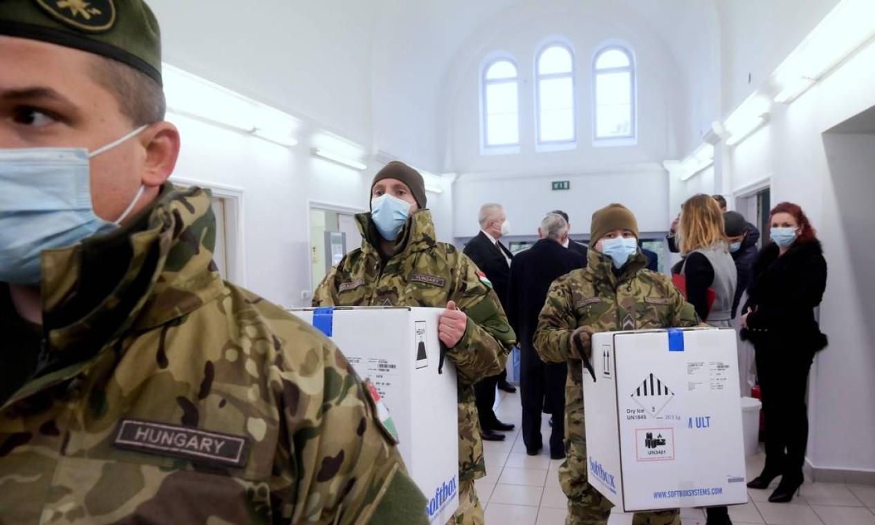 Húngaros carregam caixas da primeira remessa de vacinas Pfizer/BioNTec contra o novo coronavírus, no Hospital Central South-Pest, em Budapeste Foto: SZILARD KOSZTICSAK / AFP