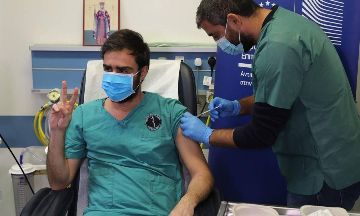 O médico Christos Kypri recebe sua primeira dose da vacina Pfizer/BioNTech COVID-19 no Hospital Geral Famagusta, na aldeia cipriota de Deryneia Foto: YIANNIS KOURTOGLOU / AFP