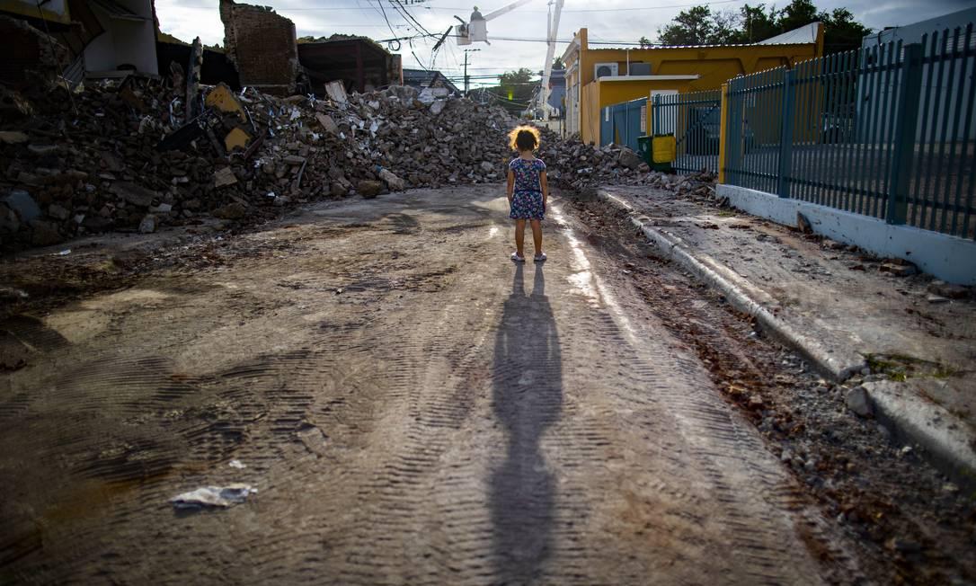 Horas após a celebração do Dia dos Três Reis, Porto Rico acordou com um terremoto de 6,4º, que causou uma crise humanitária nas cidades do sudoeste da ilha. No dia seguinte, os incrédulos porto-riquenhos saíram para observar os danos catastróficos. Entre eles, a pequena Isabella Santiago, que caminhava confusa entre os escombros que restaram em seu bairro, na rua Rufina, no município de Guayanilla Foto: Ramón Tonito Zayas / El Nuevo Día/Puerto Rico/GDA