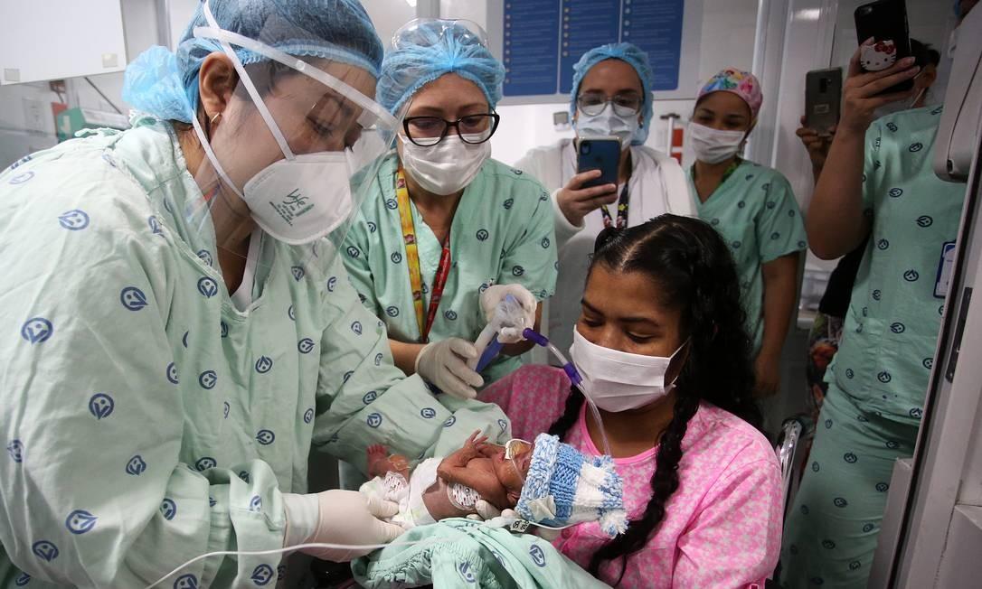 Diana Paola Angulo Mosquera, 36 anos, segura o filho recém-nascido na clínica Versalles, em Cali, na Colômbia. Ela chegou ao hospital infectada com coronavírus e com 24 semanas de gestação. Após apresentar piora no seu quadro clínico, precisou ser entubada e entrou em coma induzido para uma cesariana de urgência quando estava com 27 semanas de gravidez, e seu filho, com 875 gramas. No dia 22 de junho, ela superou a covid-19 e, após 21 dias, pôde conhecer Jefferson, que hoje respira sem ajuda de aparelhos e ganha peso a cada dia Foto: Juan Pablo Rueda / El Tiempo/Colombia/GDA
