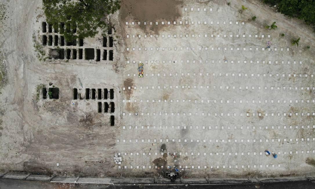 Funcionários colocam uma placa em túmulos de vítimas da covid-19 no cemitério municipal de La Bermeja, em San Salvador, El Salvador, em outubro de 2020 Foto: Javier Aparicio / La Prensa Gráfica/El Salvador/GDA