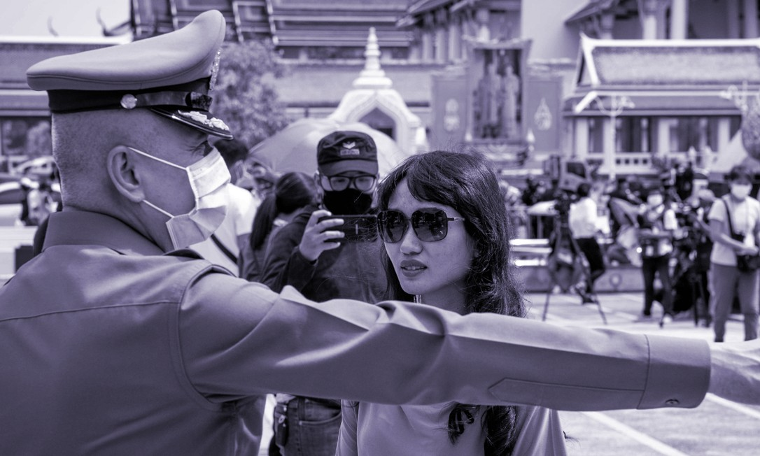 """Na foto (23.08/2020), um policial se dirige à ativista Chonticha """"Lookate"""" Jangrew, representante do Free People Group, durante uma manifestação pela democracia na Tailândia. Durante 2020, a pandemia de Covid-19 colocou as mulheres diante de novos desafios que seguirão em 2021. Ativistas e organizações internacionais temem que retrocessos recentes eliminem anos de progressos. Foto: Mladen ANTONOV / AFP"""