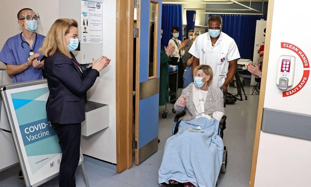 Annie Lynch, uma mulher de 79 anos de Dublin, é aplaudida pela equipe após se tornar a primeira pessoa a receber a vacina Pfizer BioNTech COVID-19 no St James's Hospital ao lado de profissionais de saúde do hospital que foram também vacinados Foto: MARC O'SULLIVAN / AFP