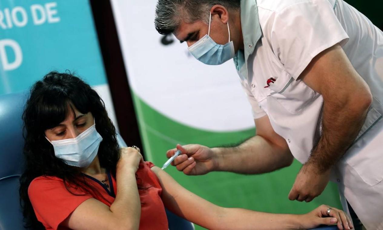 Estefania Zeurnja, 29, é inoculada com dose da vacina russa Sputnik V contra o coronavírus, no hospital Dr. Pedro Fiorito, em Avellaneda, arredores de Buenos Aires, Argentina. O país, que iniciou sua campanha de imunização nesta terça-feira, é o primeiro das Américas a usar o imunizante produzido pela Rússia Foto: AGUSTIN MARCARIAN / REUTERS