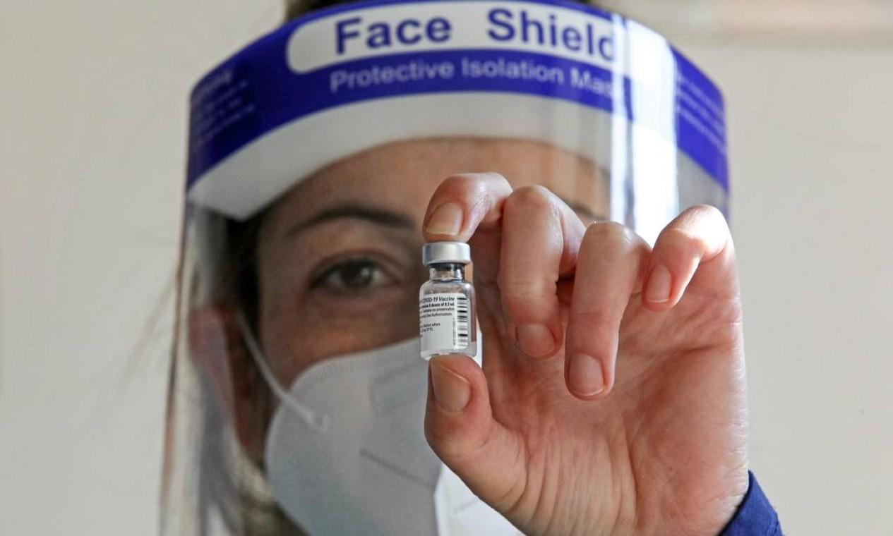 Um profissional de saúde segura um frasco da vacina Pfizer-BioNTech COVID-19 na casa de saúde Protypos Nikios Xenonas, em Nicósia, Chipre Foto: CHRISTINA ASSI / AFP