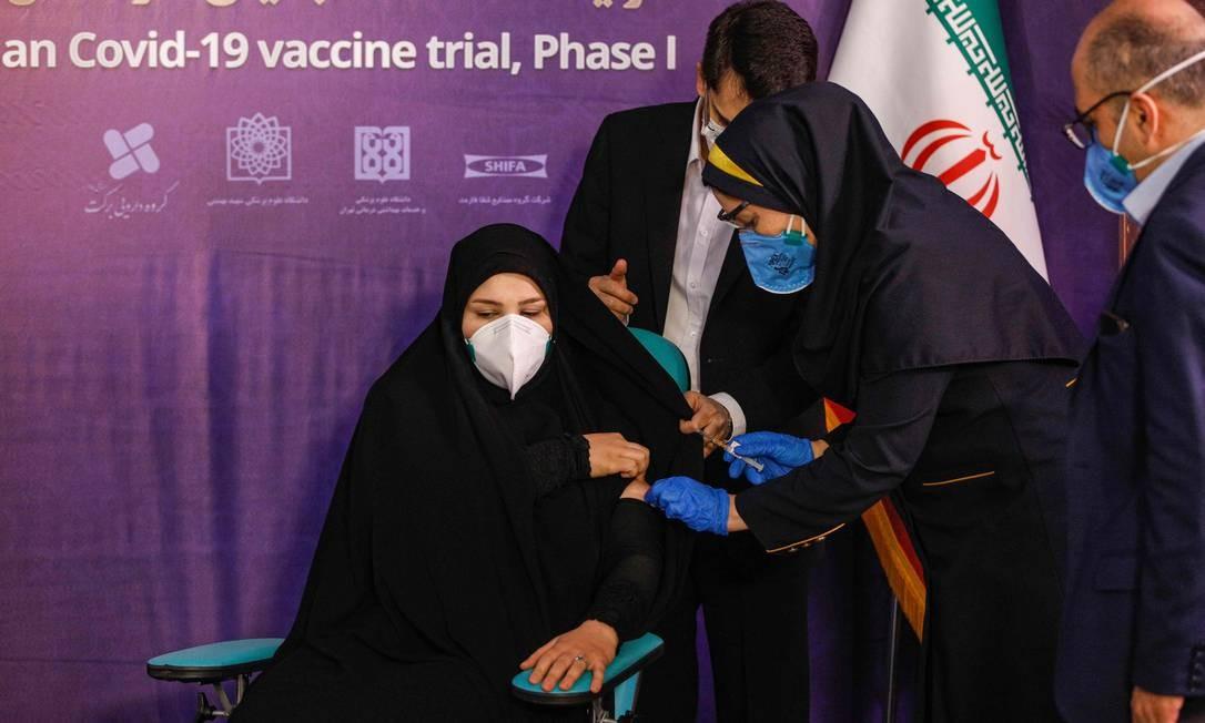 Mulher recebe uma injeção durante a primeira fase de ensaio de uma vacina iraniana produzida localmente contra o coronavírus na capital do Irã, Teerã Foto: - / AFP