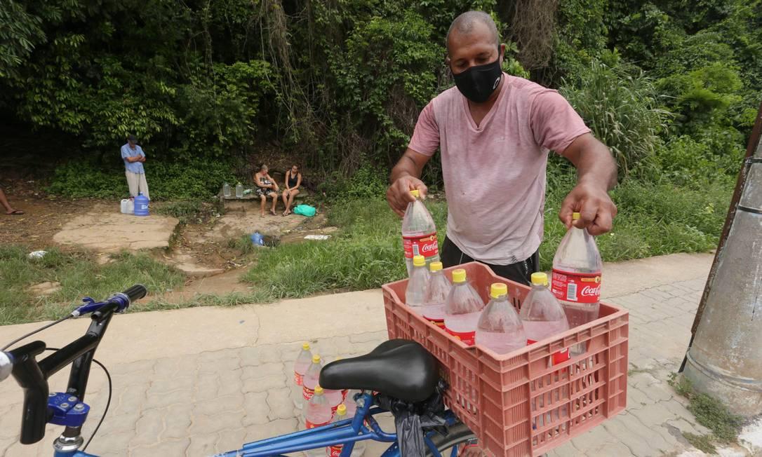 Mina de água no bairro São Jorge, em Japeri, na Baixada Fluminense, salva moradores como Edson Vander, de 46 anos, que estão sem água em casa Foto: Cléber Júnior