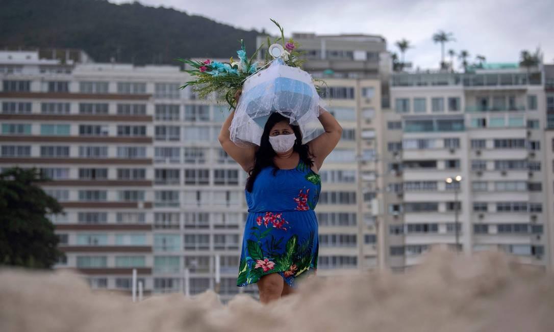 Mulher carrega barco com oferenda de fim de ano a Iemanjá, considerada a Deusa do Mar na Umbanda, na Praia de Copacabana, no Rio de Janeiro Foto: MAURO PIMENTEL / AFP