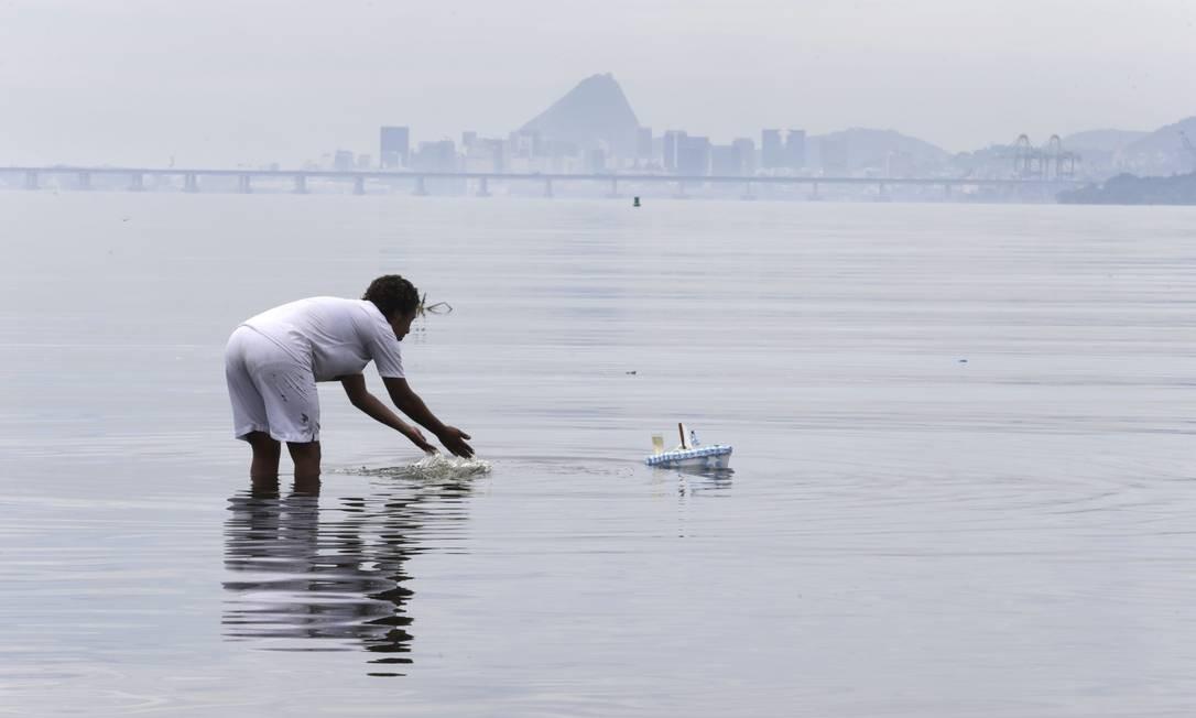 Devoto coloca oferenda para Iemanjá na praia do Galeão Foto: Domingos Peixoto / Agência O Globo
