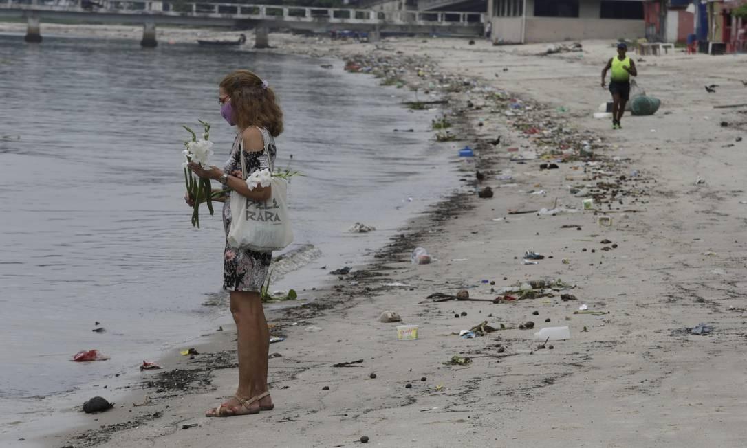 Devota joga flores na Praia do Galeão Foto: Domingos Peixoto / Agência O Globo