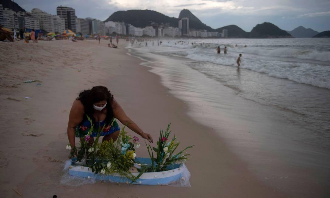 Uma adoradora de Iemanjá coloca no mar de Copacabana um barco com oferendas para a orixá. Ritual tradicional nas passagens de ano Foto: MAURO PIMENTEL / AFP