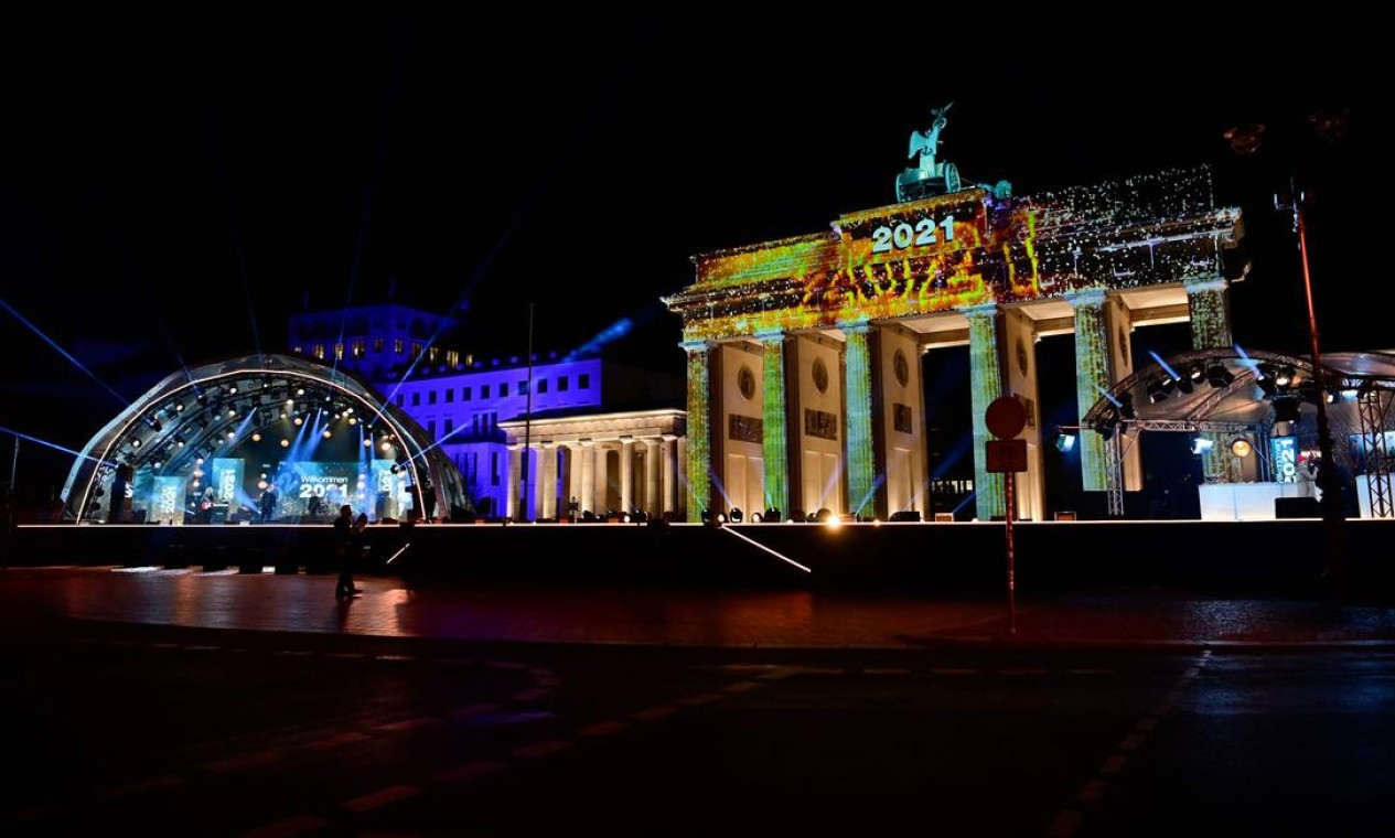 O Portão de Brandemburgo é iluminado com a inscrição '2021' enquanto artistas se apresentam durante o concerto 'Willkommen 2021' (Bem-vinido 2021) na véspera de Ano Novo Foto: JOHN MACDOUGALL / AFP
